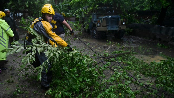 Joshua Alicea, a rescue staff member from the Municipal Emergency Management Agency, removes a tree while searching for people in trouble during the passage of Hurricane Irma through the northeastern part of the island in Fajardo, Puerto Rico.