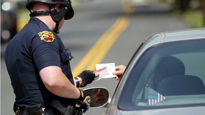 Elmwood Park Police Officer Andrew Draing checks registration and insurance of a driver he had pull to the side of the road for not wearing a seat belt. Draing let him go with a verbal warning June 15, 2004.