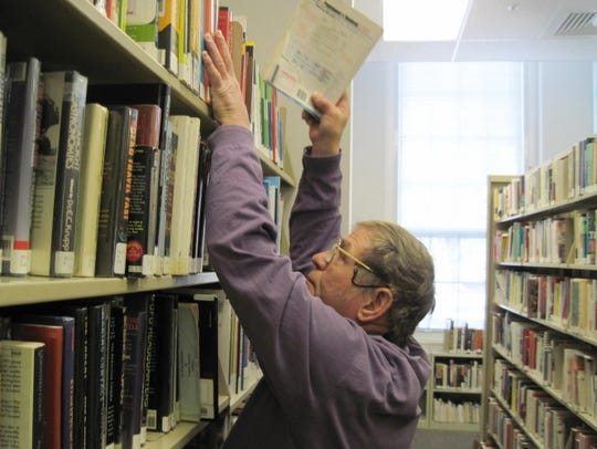 Gary Kiracofe puts books back on the shelves at the