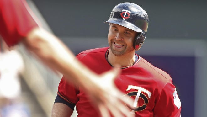 The Minnesota Twins' Brian Dozier smiles as the third base coach reaches out to congratulate him as he jogs the base path on a solo home run off Kansas City Royals pitcher Ian Kennedy in the first inning Monday in Minneapolis.