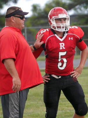 Riverheads coach Robert Casto, left, gives a play to quarterback Chase Armstrong during their scrimmage against Appomattox on Aug. 20, 2016.