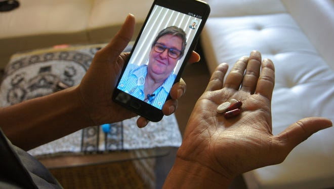 In this March 15, 2018 photo, public health nurse Peggy Cooley of the Tacoma-Pierce County Health Department, seen on the phone screen, uses Skype video to remotely monitor a patient taking antibiotics for tuberculosis at home in Lakewood, Wash. Researchers are testing how well smartphone apps that monitor pill-taking work when medication matters. Experts praise the efficiency, but some say the technology raises privacy and data security concerns.