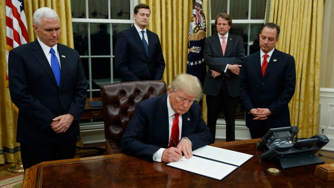 President Trump, flanked by Vice President Pence and chief of staff Reince Priebus, signs an executive order on health care on Friday.