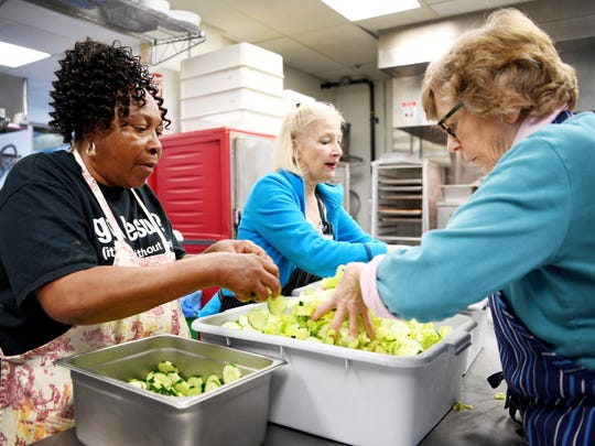 From left, Mary Littlejohn, Margaret Gourdin and Barbara Henderson prepare salad for a meal at Haywood Street Congregation Welcome Table November 15, 2017.