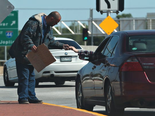 A motorist gives a panhandler money on North Kansas