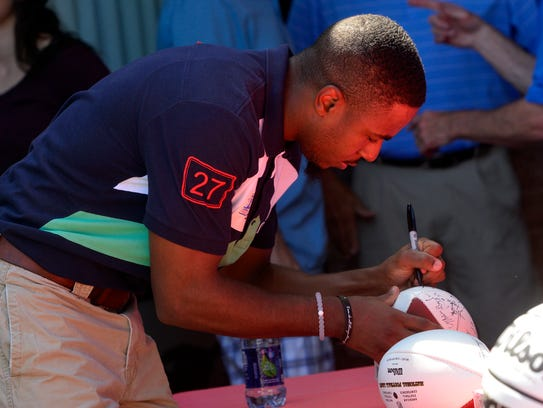 Darius Jennings of the Cleveland Browns signs footballs