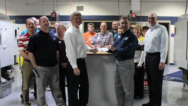 Gene Haas representatives present a check to LTC Executive Dean Rich Hoerth, President Michael Lanser, staff and CNC students.