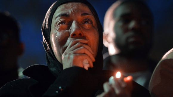 A woman cries during a vigil as she watches photos projected on a screen of three people who were killed. (AP Photo/The News and Observer, Chuck Liddy)
