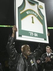 Former Seattle SuperSonic Gus Williams displays his No. 1 jersey to the crowd during halftime ceremonies Friday, March 26, 2004, in Seattle. Williams, who led the SuperSonics to the 1979 NBA championship, had his jersey retired during halftime of the Sonics-Denver Nuggets game.