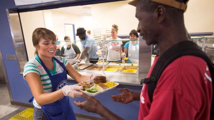 Volunteer Fransisca Gonzalez serves a hot lunch to Robert Lewis at the St. Vincent de Paul dining room in Phoenix last week.