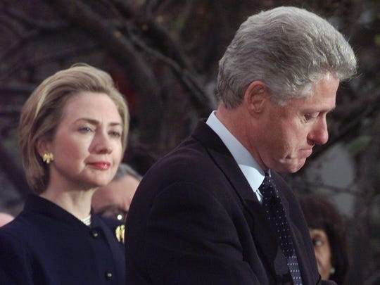 First lady Hillary Clinton looks on as President Bill Clinton makes a statement at the White House on Dec. 19, 1998, following his impeachment by the House.