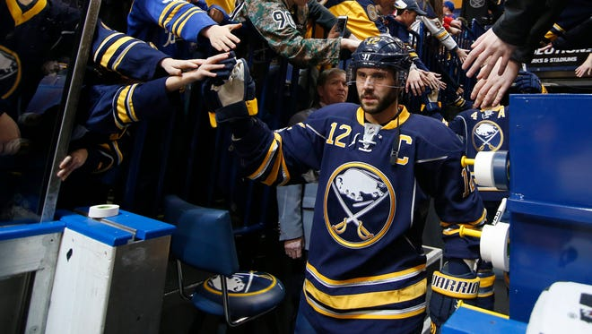Buffalo Sabres right winger Brian Gionta  greets fans while walking to the ice prior to his 1000th career game Monday night. To cap the night, the Greece native scored a goal in the second period
