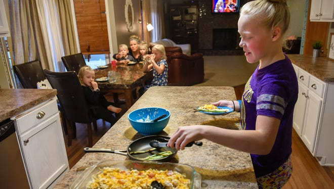 Lilly Morrell, 12, dishes up seconds during a dinner of high-fat, low-carb and low-sugar foods with her family Monday, Nov. 13, in Monticello. Dinner is a chicken and bacon casserole, mashed cauliflower with bacon and cheese, and asparagus seared in bacon.