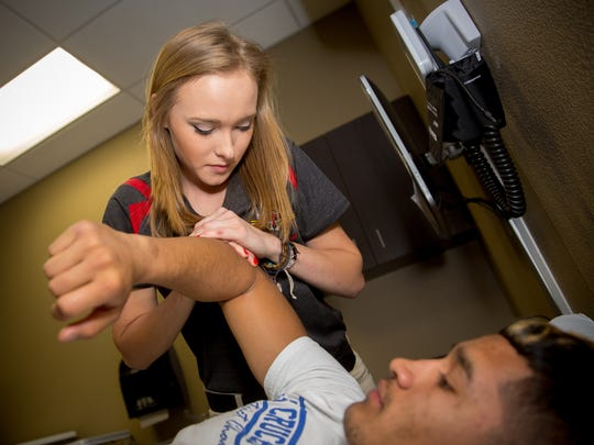 Centennial High School student Katrina Keding conducts an orthopedic exam on Las Cruces High School student Brandon Baeza at the Arrowhead Park Medical Academy on March 2, 2016.