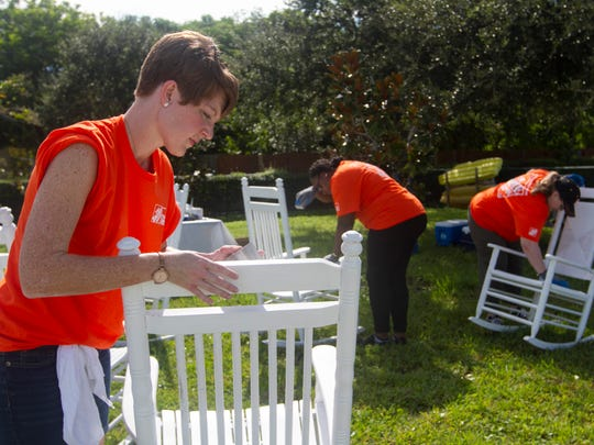 Volunteers Holly Santiago, left, Bola Ketiku and Patti Olmsted sand rocking chairs at Lifeline Family Center before painting them on Wednesday in Cape Coral. Volunteers from Home Depot also renovated the kitchens in the home for young mothers.