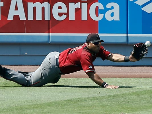 Arizona Diamondbacks left fielder Yasmany Tomas dives but cannot catch an RBI double by Los Angeles Dodgers' Yasiel Puig during the fifth inning of a baseball game in Los Angeles, Sunday, July 31, 2016. The Dodgers won 14-3. (AP Photo/Alex Gallardo)