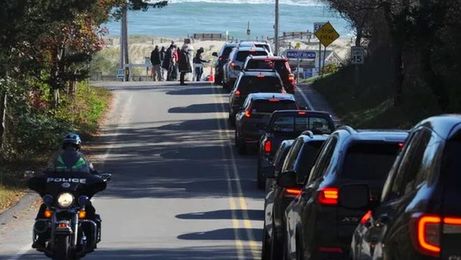Cars line up to enter Nauset Beach parking lot for Saturday's town meeting.