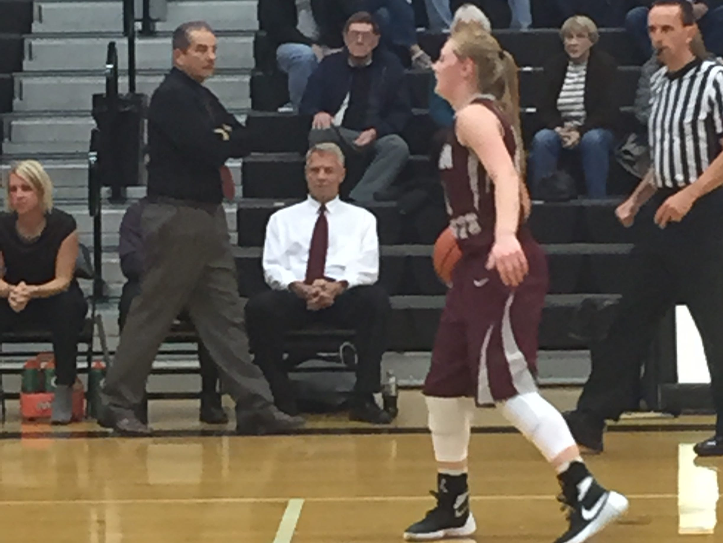 Genoa's Haley Pickard handles the ball Friday as coach Mike DeStazio walks the sideline in an NBC victory over Otsego.