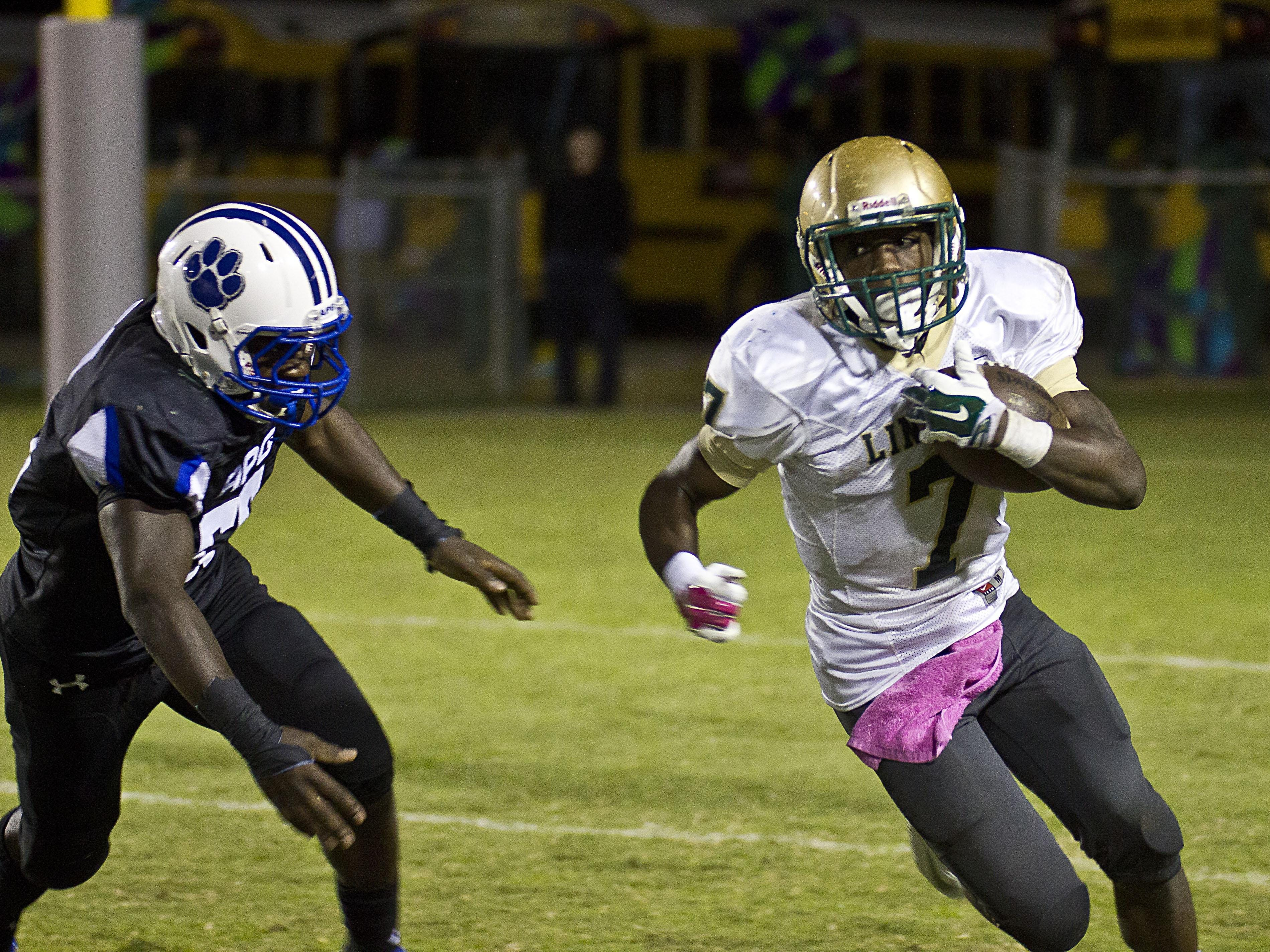 Lincoln running back Ricky Henrilus goes for a gain against Godby during last year's 22-17 loss to the Cougars.