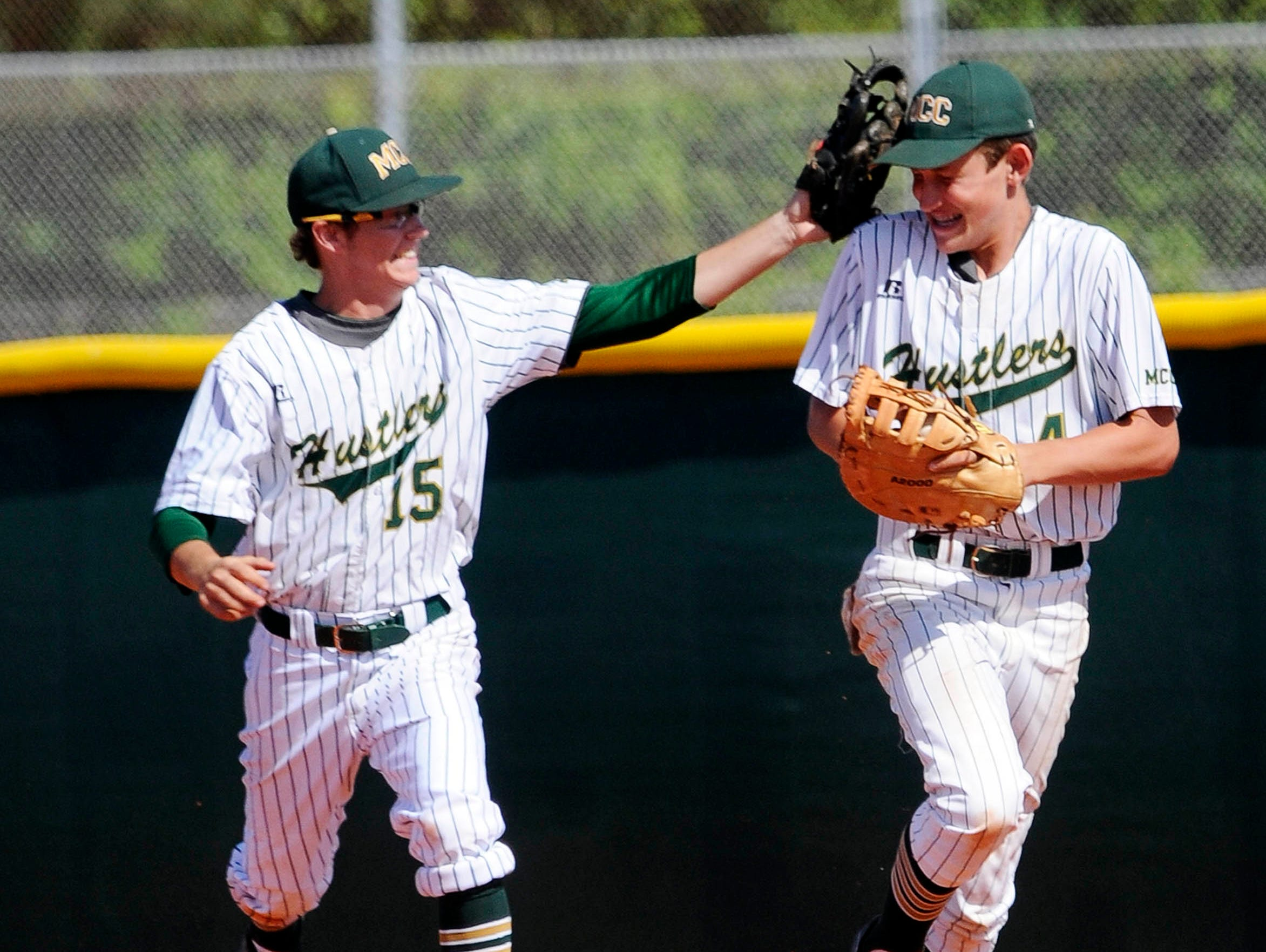 MCC's Colman LalRoche high fives teammate Nick Durgin during Wednesday's game in Melbourne.