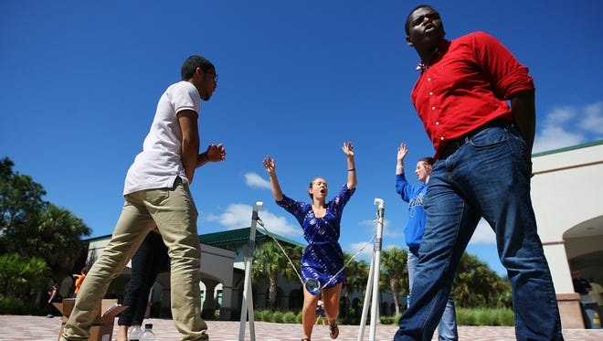 Estero High School's Amanda Patterson, 18, celebrates with her team after a successful catapult launch During the STEM@Work wrap-up session Wednesday at FGCU.