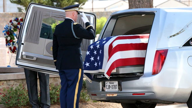 A member of a military honor guard salutes the remains of Sgt. Alexander Ruiz Martinez, a World War II and Korean War veteran, during his burial at Fort Bliss National Cemetery Monday.