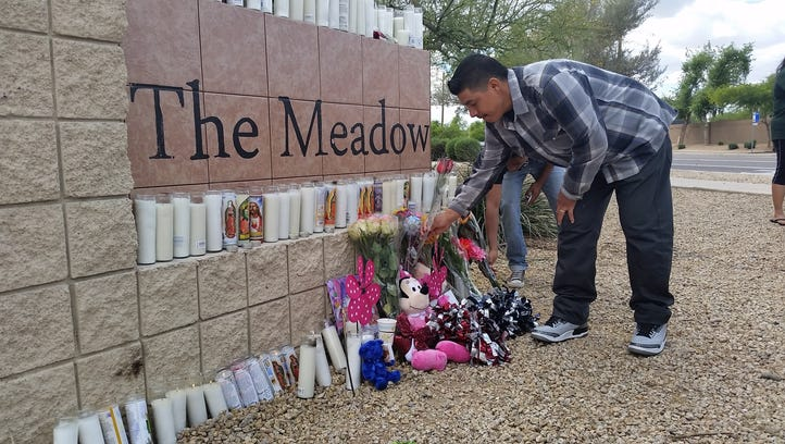 A Sierra Linda High School student places flowers at