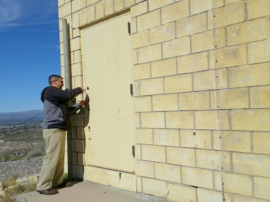"Henry Espalin, assistant director for facilities at NMSU, locks up a building known as the AT&T Building on top of Tortugas ""A"" Mountain during a tour of the site Nov. 11. The decades-old structure, which once housed radio communications equipment, is set for demolition."