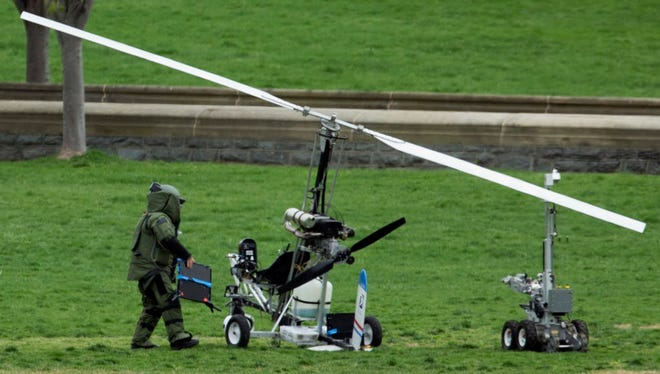 A member of a bomb squad checks a small helicopter after a man landed on the West Lawn of the Capitol in Washington on April 15, 2015.