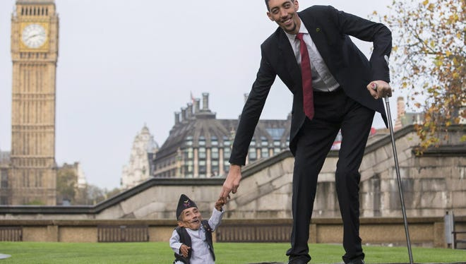 Chandra Bahadur Dangi, from Nepal, (L) the shortest adult to have ever been verified by Guinness World Records, poses for pictures with the world's tallest man Sultan Kosen from Turkey, during a photocall in London on November 13, 2014, to mark Guinness World Records Day.