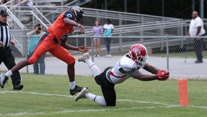 Greenville's Danyaus Williams-Byrd (5) reaches for the goal line while being chased by Carolina's Tyreek Williams (8).