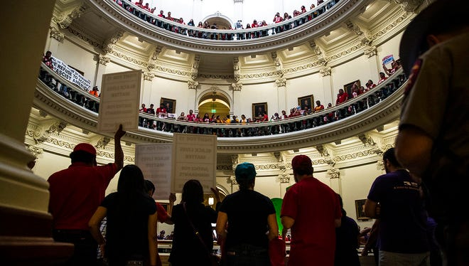 Hundreds of protesters line the balconies of the state Capitol rotunda in Austin on Monday, May 29, 2017 the last day of the legislative session, to protest Senate Bill 4, legislation already passed by Texas Gov. Greg Abbott that compels local police to enforce federal immigration law. (Ricardo Brazziell/Austin American-Statesman via AP)