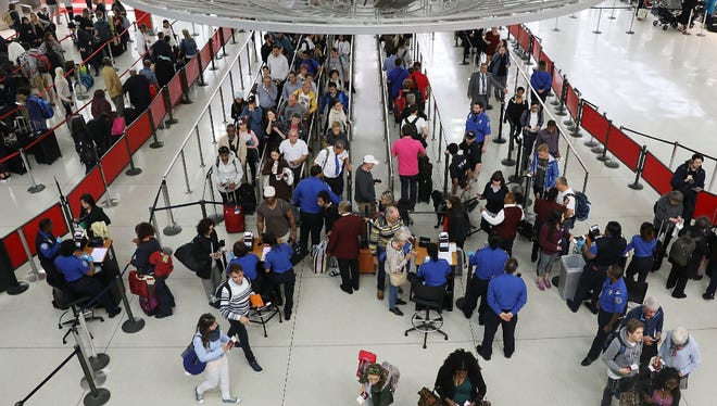 """People wait in line at John F. Kennedy International Airport (JFK) on June 5, 2017 in New York City. Part of what the White House is calling the president's """"infrastructure week,"""" President Donald Trump announced Monday a plan to privatize the nation's air traffic control system. If enacted, it would remove the job of tracking and guiding airplanes from the oversight of the Federal Aviation Administration."""