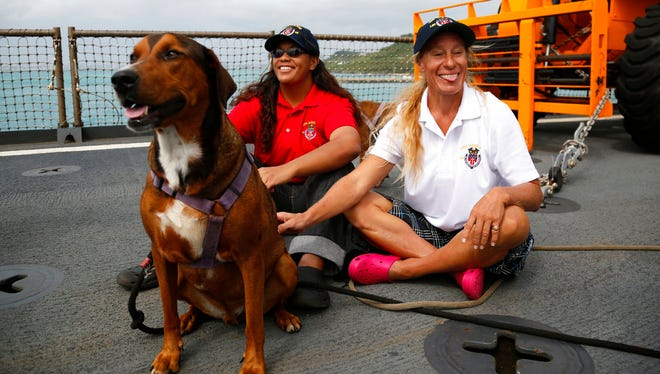 Jennifer Appel, right, and Tasha Fuiava sit with their dogs on the deck of the USS Ashland Monday, at White Beach Naval Facility in Okinawa, Japan.  The U.S. Navy ship arrived at the American Navy base, five days after it picked up the women and their two dogs from their storm-damaged sailboat, 900 miles southeast of Japan.  (AP Photo/Koji Ueda)