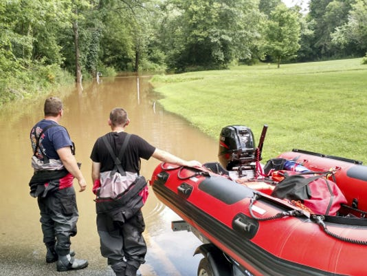 Rescuers look down a flooded Conewago Creek Road from the Bowers bridge road intersection. A pickup truck attempted to cross a 1800 foot section of flooded Conewago Creek Road between Park Street and Bowers Bridge Road Sunday June 21, 2015 in East Manchester Township. It was unsuccessful, leading to a rescue by an Eastern Regional Police officer who walked the uninjured victim out.