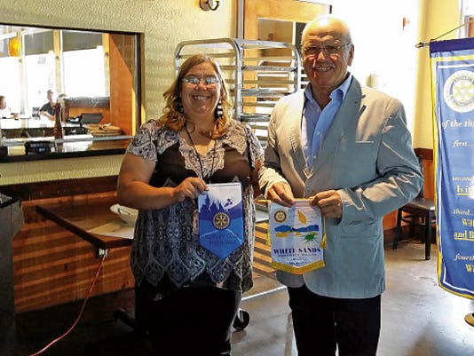 Rotary guest Gen. (ret.) Walter Jertz, of Oppenheim, Germany, in a Rotary Club banner exchange with White Sands Rotary president Renee Cantin. Gen. Jertz was instrumental in the German Luftwaffe stationing a squadron at Holloman Air Force Base.