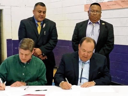 Mescalero Apache President Danny Breuninger Sr., seated right, and Mike Frueh, director of the Veterans Administration Loan Guaranty based in Washington D.C., make it official by signing a Memorandum of Understanding. In back from left are Mescalero Vice President Gabe Aguilar and Kelton K. C. Starr, education director/New Mexico Department of Veterans Services, tribal veteran representative.