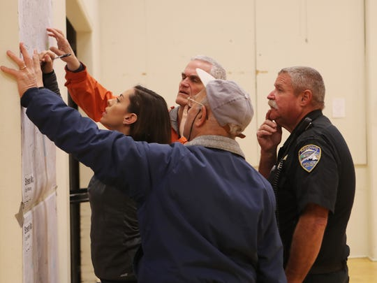 Sandra Oswald, from left, Doug McMullin, Marion Schmitz and Redding Police Community Servies Officer Bob Brannon look at a map during the Point In Time homeless count, Wednesday, in Redding at the Veterans Hall. Shasta Support Services organized this year's count.