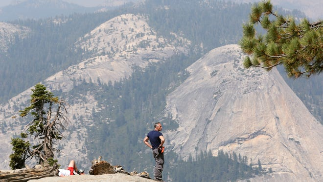 Visitors take in the sites from Glacier Point on Sunday, August 23, 2015 in Yosemite National Park, Calif.