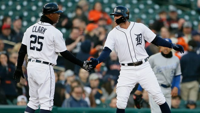 JaCoby Jones #21 of the Detroit Tigers slaps hands with third base coach Dave Clark #25 of the Detroit Tigers after hitting a stand-up double against the Kansas City Royals during the third inning of game two of a doubleheader at Comerica Park on April 20, 2018 in Detroit, Michigan.