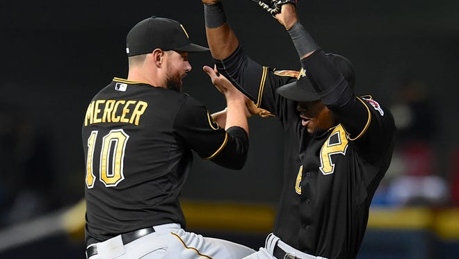 Pittsburgh Pirates shortstop Jordy Mercer (10) and left fielder Starling Marte (6) react after defeating the Atlanta Braves to secure a post season spot at Turner Field. The Pirates defeated the Braves 3-2.