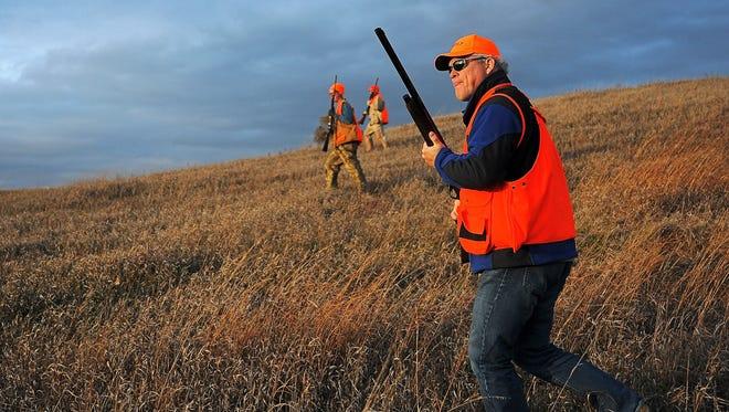 Argus Leader Media columnist Stu Whitney walks through a field while pheasant hunting with Brett Lovrien (left) and Joe Fanciullo near Mitchell.