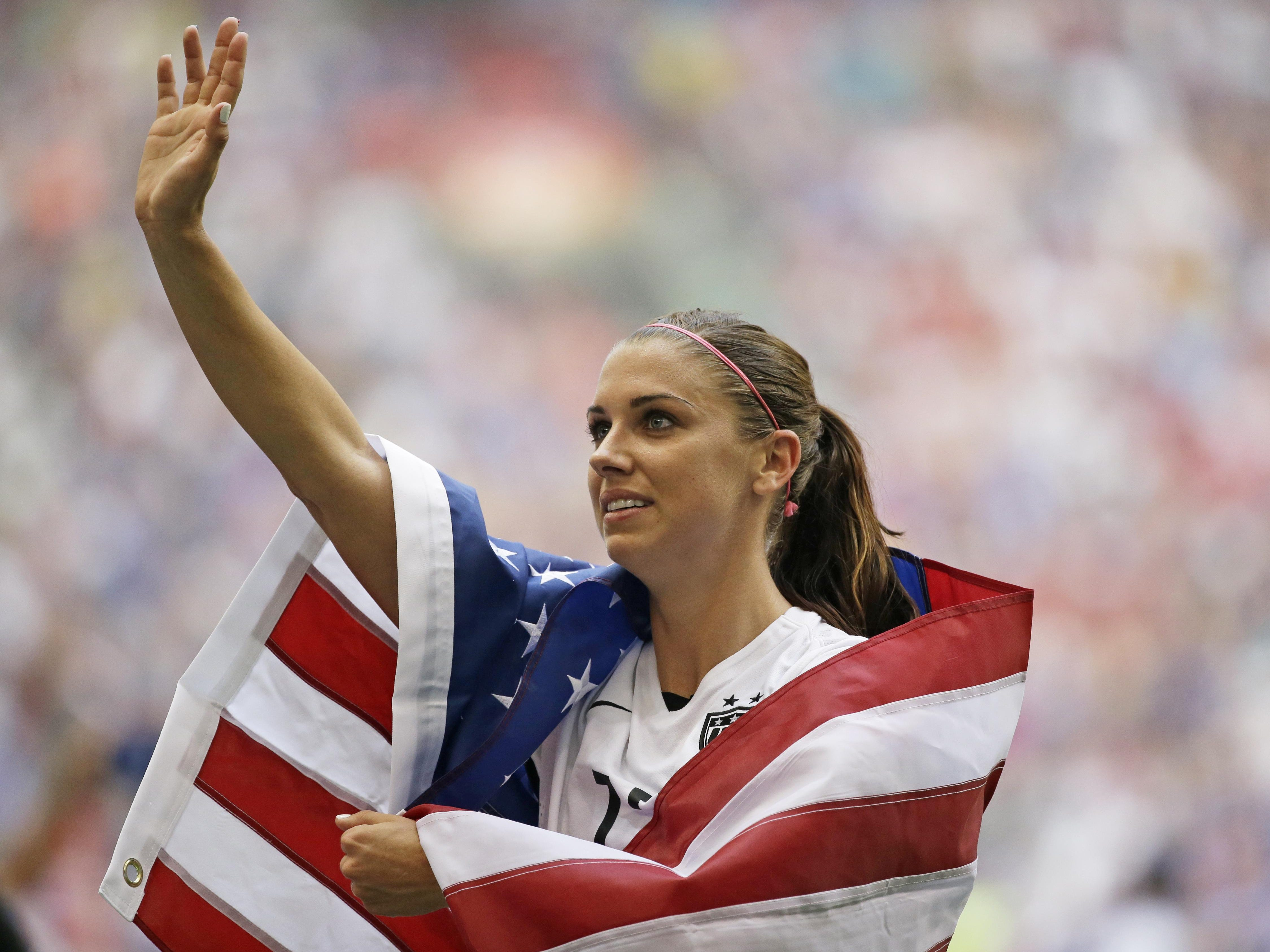 United States' Alex Morgan is draped in the U.S. flag as she waves to fans after the U.S. beat Japan 5-2 in the FIFA Women's World Cup soccer championship in Vancouver, British Columbia, Canada, Sunday, July 5, 2015.