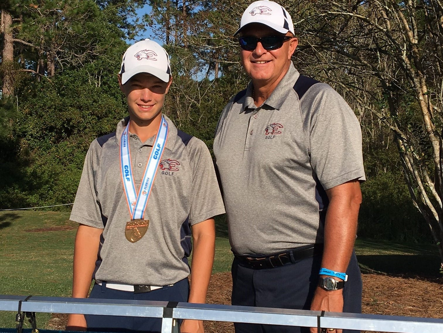 Estero's Luke Farmer and Wildcat head coach Bruce Buchla after Farmer tied for third overall at the 2A FHSAA Boys' Golf Championships at Mission Inn Resort in Howey-in-the-Hills, FL.