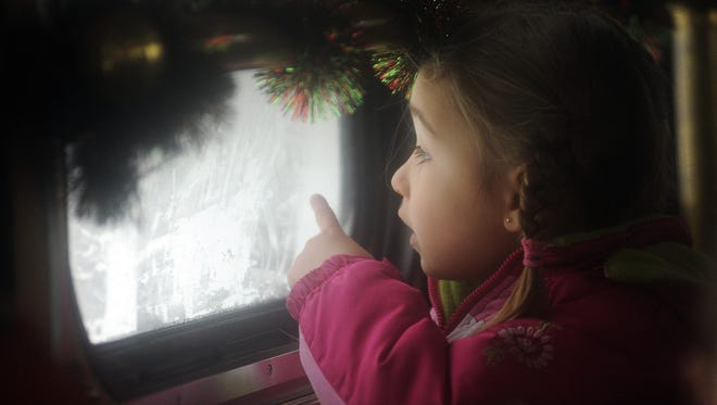"""Annah Neuser of Manitowoc looks out the steamed-up window of a Discovery trolley, where she and other passengers listen to a reading of """"The Polar Express"""" over the speakers on their trip from the Holiday Inn to the Wisconsin Maritime Museum in 2013."""