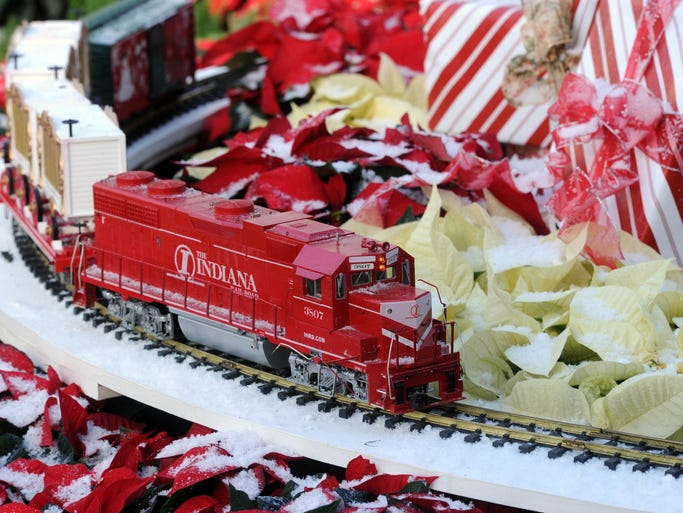 A model train rolls past poinsettias frosted with artifical snow. Model trains, twinkling lights and 500 poinsettias fill Garfield Park Conservatory during the annual Conservatory Crossing holiday display, which opened Friday November 29, 2013.