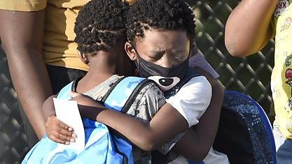 Keith Trim, from left, gives a hug to his twin brother, Vincent, both 5, as they say an emotional goodbye before heading into Wilkinson Gardens Elementary School for the first day of school at Monday morning September 8, 2020 in Augusta, Ga.