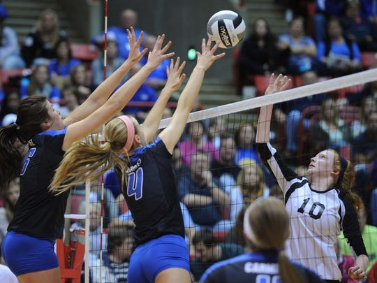 FILE - Carly Skojdt and Carly Cason of Carmel try to block a shot by Avon's Rebekah Strange. Avon defeated Carmel 3-1 in the 4A state volleyball championship game November 9, 2013 at Ball State University' Worthen Arena.