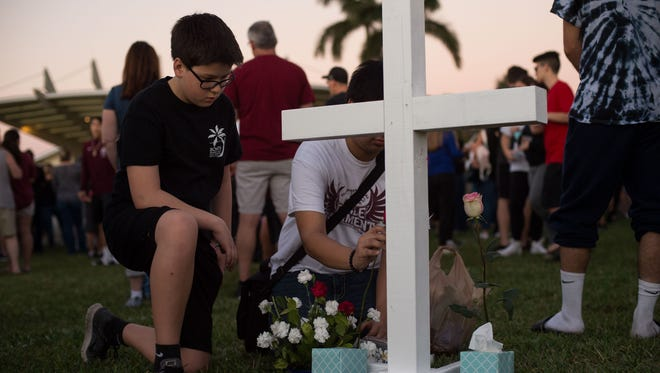 Zachary Valdes, 13, attends a candlelight vigil with his family at the Pine Trails Park amphitheater to mourn a day after a mass shooting at Marjory Stoneman Douglas High School in Parkland. Valdes was at neighboring Westglades Middle School when the two campuses went on lockdown.