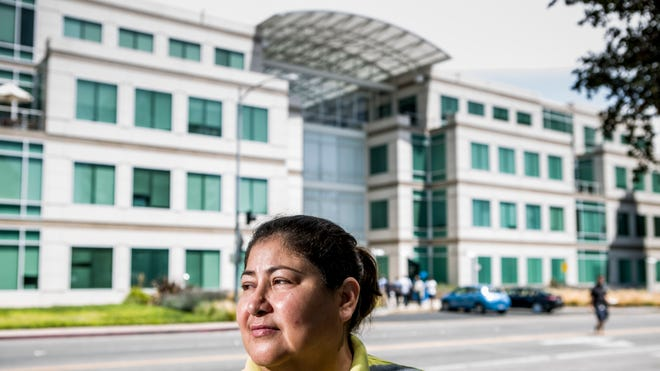 Eulogia Figueroa, 49, a janitor at Apple, in front of the Apple campus in Cupertino, Calif. She earns $14.94 an hour, barely enough to scrape by in Silicon Valley.